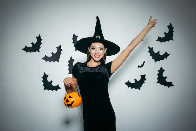 Donna sorridente con zucca e cappello di halloween