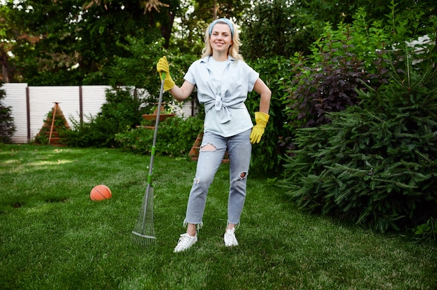 Smiling woman with rake works in the garden. female gardener takes care of plants outdoor, gardening hobby, florist lifestyle and leisure
