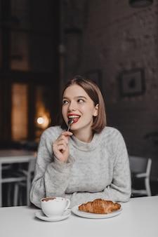 La donna sorridente con il rossetto rosso sta leccando il cucchiaino. ragazza in abito di cashmere godendo di croissant.