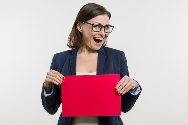 Smiling woman with red sheet of paper
