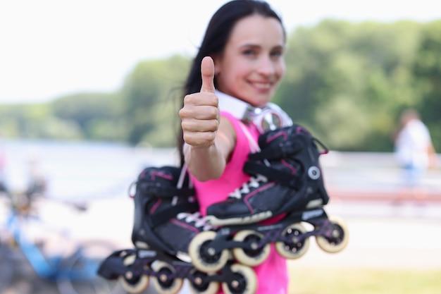 Улыбающаяся женщина с роликами на плече показывает большой палец вверх крупным планом продажи концепции спортивных товаров