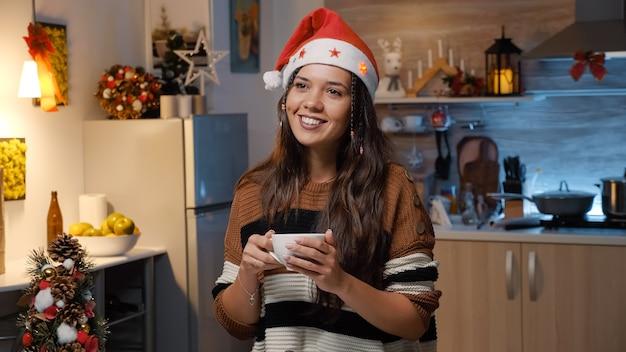 お祝いのキッチンでサンタ帽子と笑顔の女性