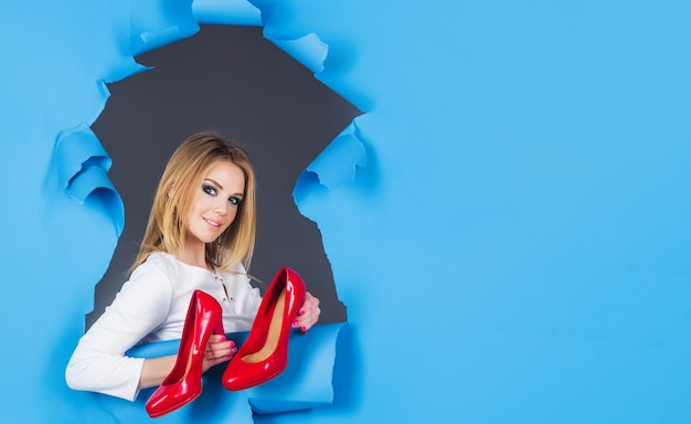 紙の穴を通して見ている靴と笑顔の女性。ファッション。モール、ショップ、または店舗でのショッピング。広告。割引と販売。