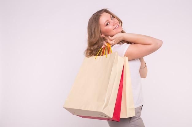 흰색 표면에 쇼핑백 함께 웃는 여자