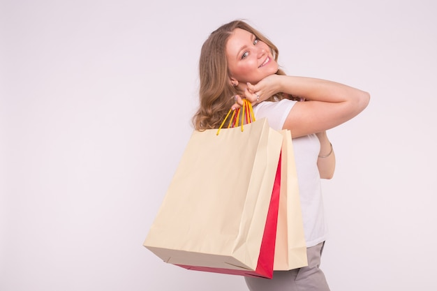 Smiling woman with shopping bags on white surface