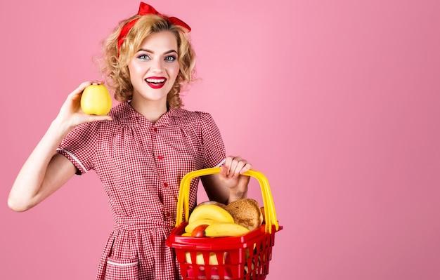 쇼핑 바구니와 사과 손에 웃는 여자. 슈퍼마켓에 행복 한 소녀입니다. 구매 흥청망청. 장바구니와 여성입니다.