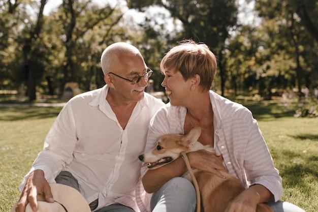 Donna sorridente con acconciatura moderna corta in camicetta rosa e jeans ridendo, abbracciando il cane e seduto sull'erba con l'uomo con i capelli grigi nel parco.