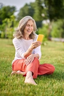 Улыбающаяся женщина со смартфоном, сидя на траве