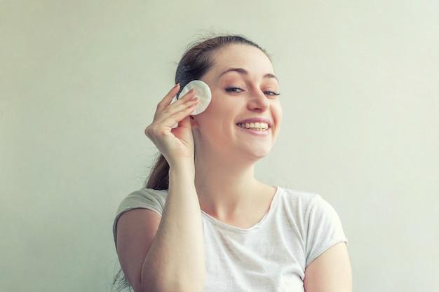 白い背景で隔離の綿パッドで補う柔らかな健康的な皮膚の除去と笑顔の女性