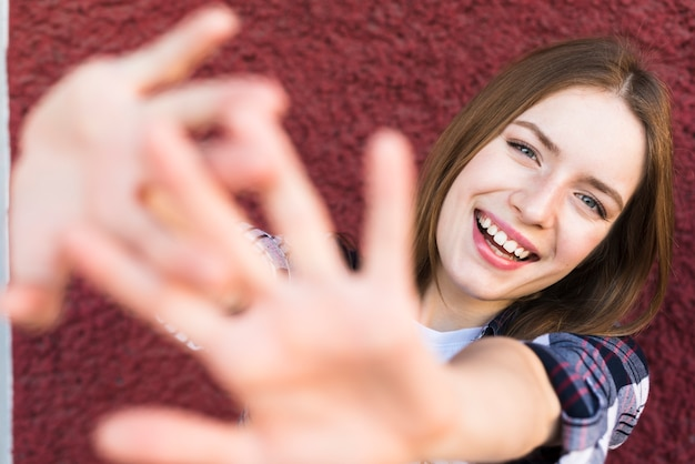 Smiling woman with stop gesture against red wall