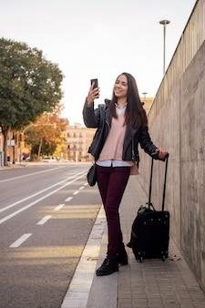 Улыбающаяся женщина с чемоданом делает видеозвонок