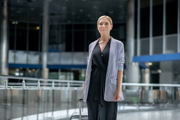 Улыбающаяся женщина с чемоданом гуляет в аэропорту