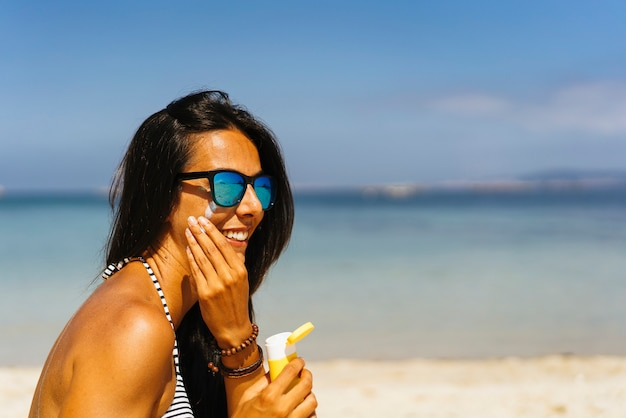 Smiling woman with sunglasses applying sun protection cream on her face in the beach
