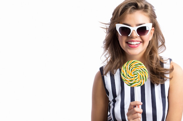 Smiling woman with sunglasses holding a lollipop.