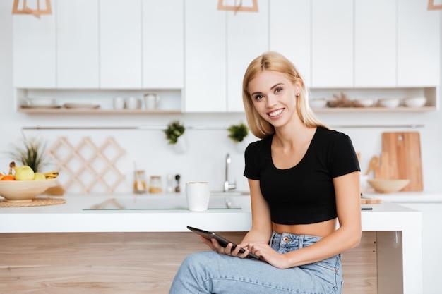 キッチンでタブレットコンピューターを持つ女性の笑みを浮かべてください。