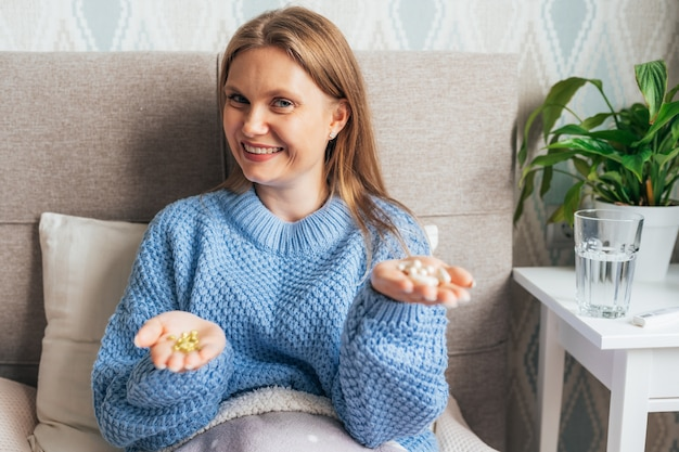 Smiling woman with two different types of pills in her hands on bed at home.