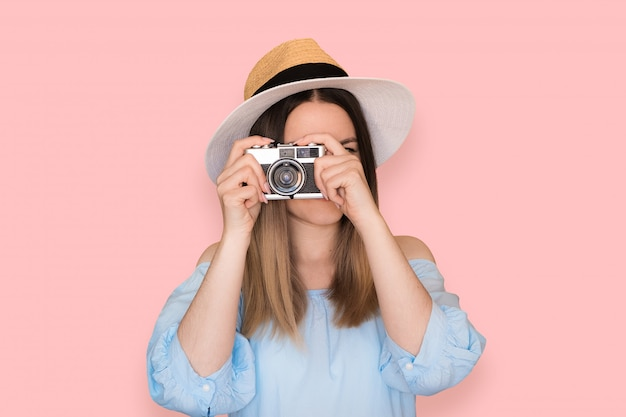 Smiling woman with vintage camera in blue dress on pink