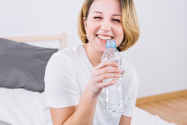 Donna sorridente con bottiglia d'acqua
