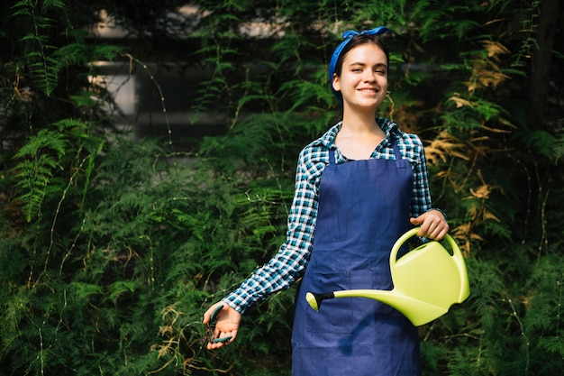 Smiling woman with watering can pruning plant with secateurs