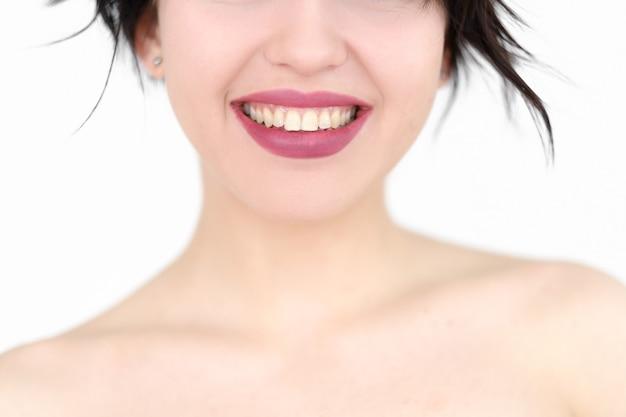Улыбается женщина с белыми зубами на белой стене.