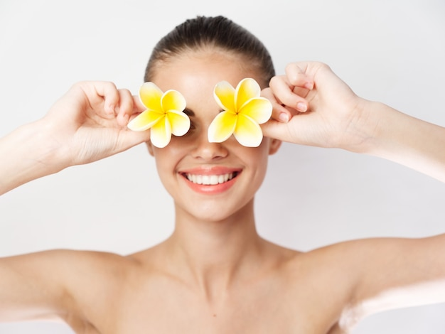 顔の裸の肩の近くに黄色い花を持つ笑顔の女性は肌をきれいにします