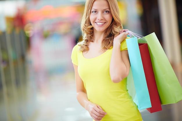 Donna sorridente con t-shirt e giallo shopping bags