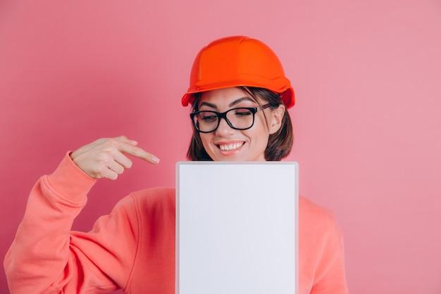 Il costruttore sorridente dell'operaio della donna tiene il bordo bianco del segno in bianco contro fondo rosa. casco da costruzione. punta il dito indice.