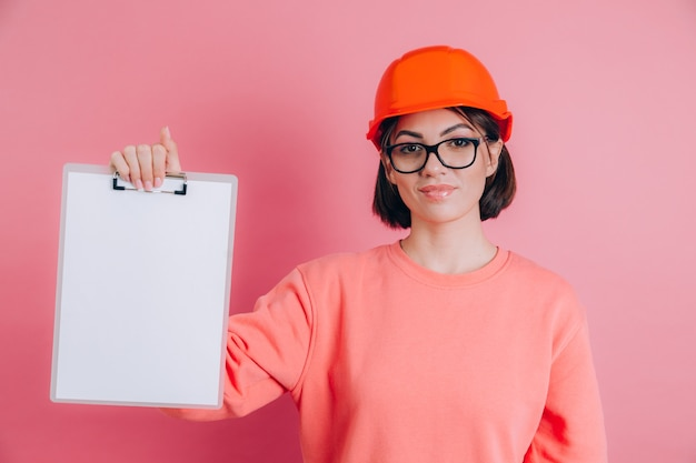 Усмехаясь пробел доски вывески владением строителя работника женщины белый против розового фона. строительный шлем.