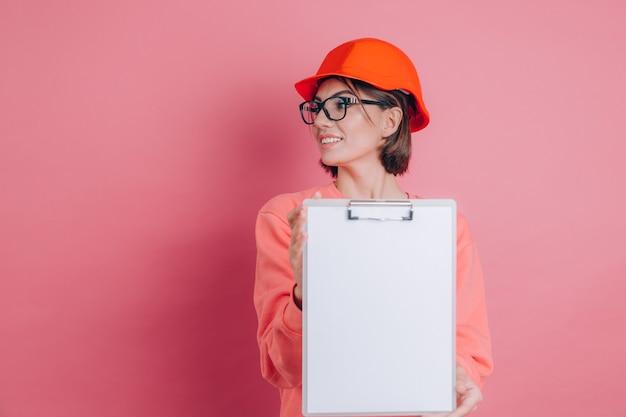 Il costruttore sorridente dell'operaio della donna tiene il bordo bianco del segno in bianco contro fondo rosa. casco da costruzione.