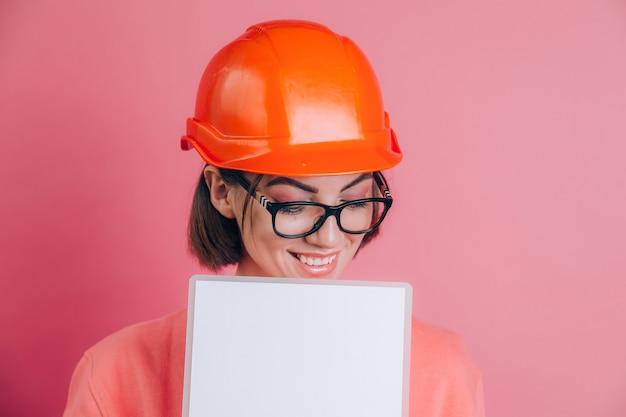 웃는 여자 작업자 작성기 분홍색 배경에 흰색 사인 보드를 빈 개최. 건물 헬멧.