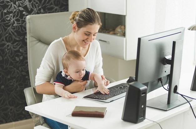 家で働いて、膝の上に彼女の赤ん坊の息子を保持している笑顔の女性