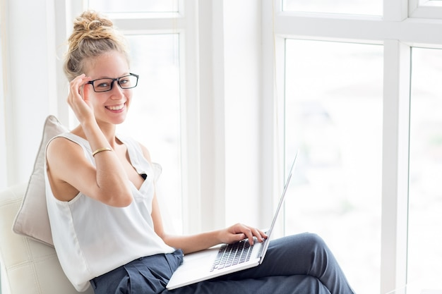 Smiling woman working on laptop at windows