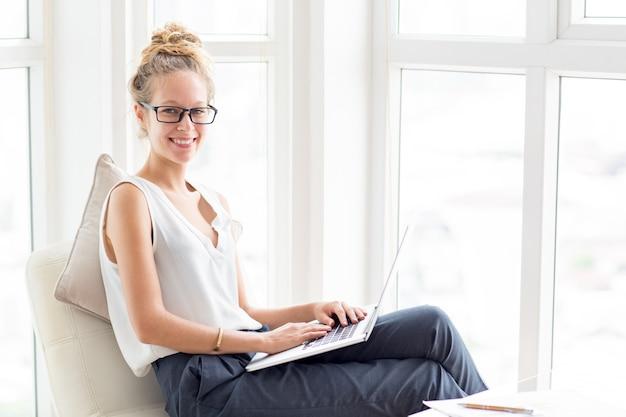 Улыбающаяся женщина, работающая на ноутбуке на лоджии