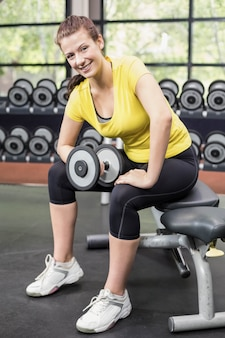 Smiling woman working out with dumbbells at crossfit gym