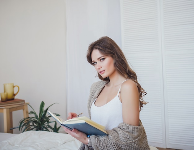 Smiling woman writing in book