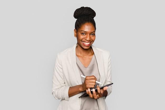 Donna sorridente che scrive note sul dispositivo digitale tablet