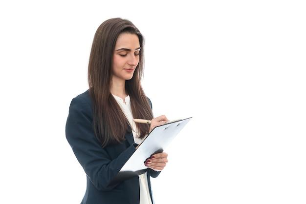 白い壁に分離されたクリップボードに書く笑顔の女性