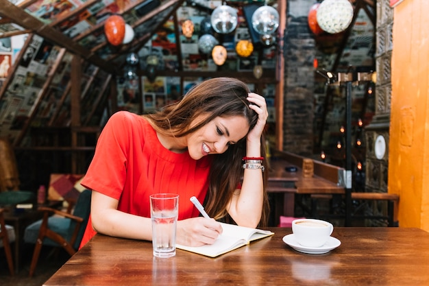 Smiling woman writing schedule in diary with cup of coffee on desk