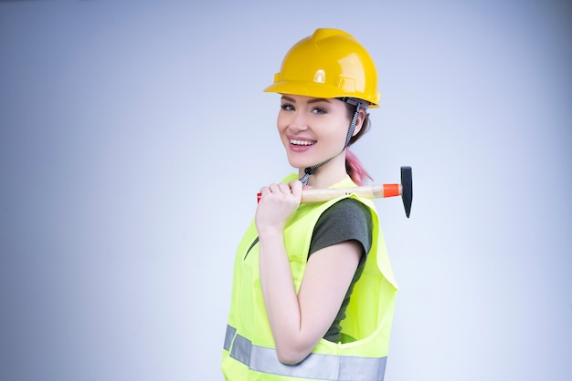 Smiling woman in a yellow helmet stands with a hammer on her shoulder