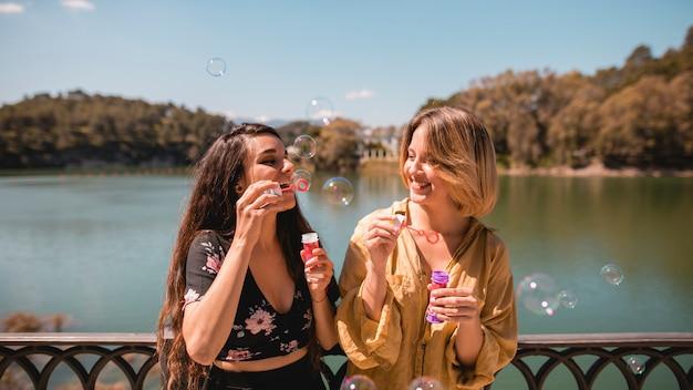 Smiling women blowing bubbles
