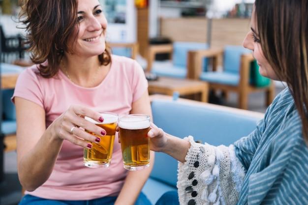 Smiling women clinking glasses