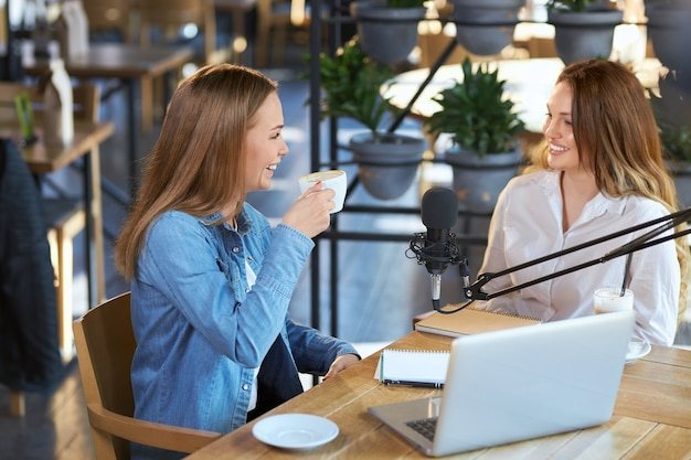 Smiling women communicating with tasty coffee in cafe