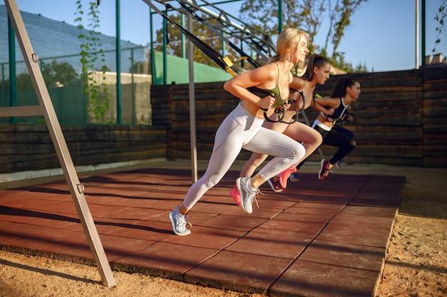 屋外のスポーツグラウンドで運動をしている笑顔の女性、屋外でのグループフィットネストレーニング