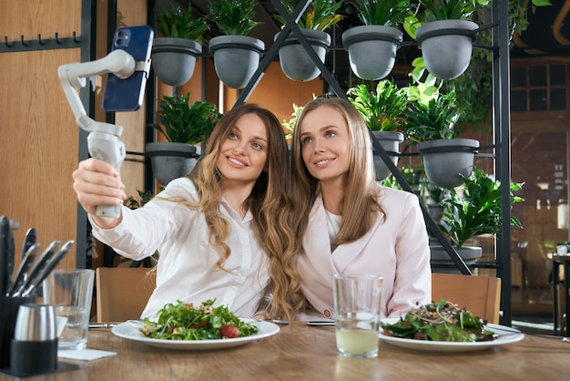 Smiling women doing selfie with modern phone in cafe