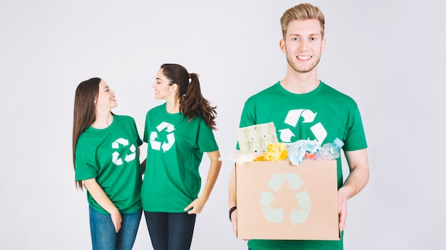 Smiling women behind happy man holding cardboard box with recycle items
