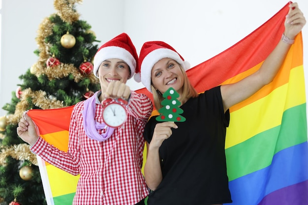 Smiling women hold lgbt flag and alarm clock on background of christmas tree family traditions