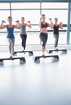 Улыбающиеся женщины, поднимающие тяжести при занятиях аэробикой