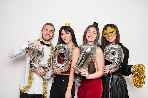 Smiling women and man in evening wear with balloons numbers