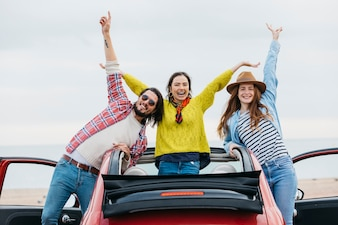 Smiling women near happy man with upped hands leaning out from car