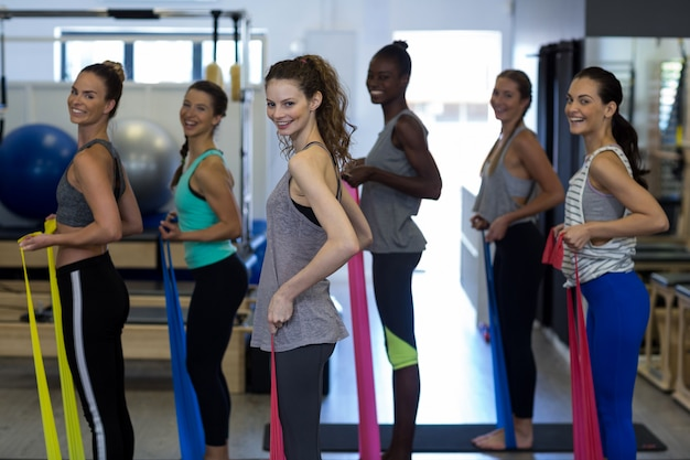 Улыбающиеся женщины выполняют упражнения на растяжку с лентой сопротивления